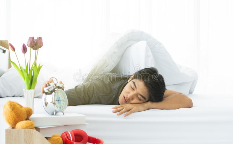 A young man is waking up in the morning while the clock alarms stock image