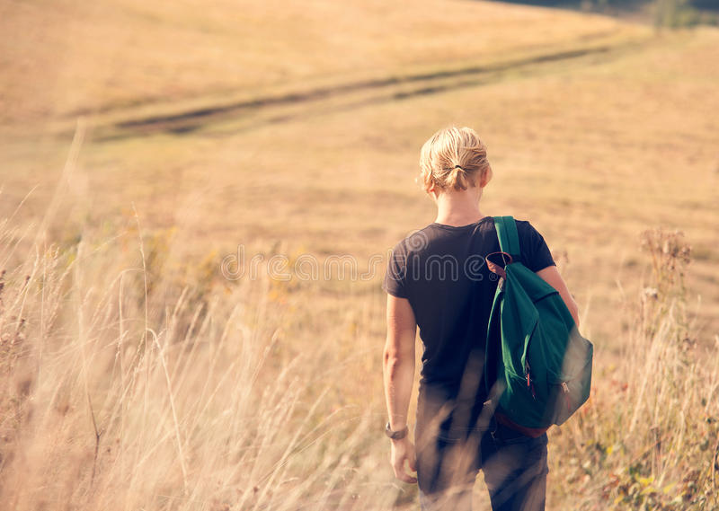 Young man walk on country side stock image