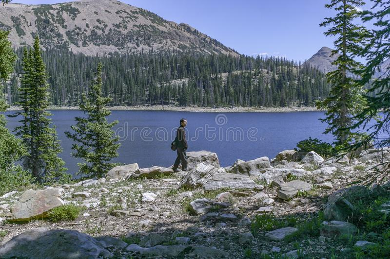 Young man walking along a trail with a mountain lake and mountains in the background royalty free stock photography