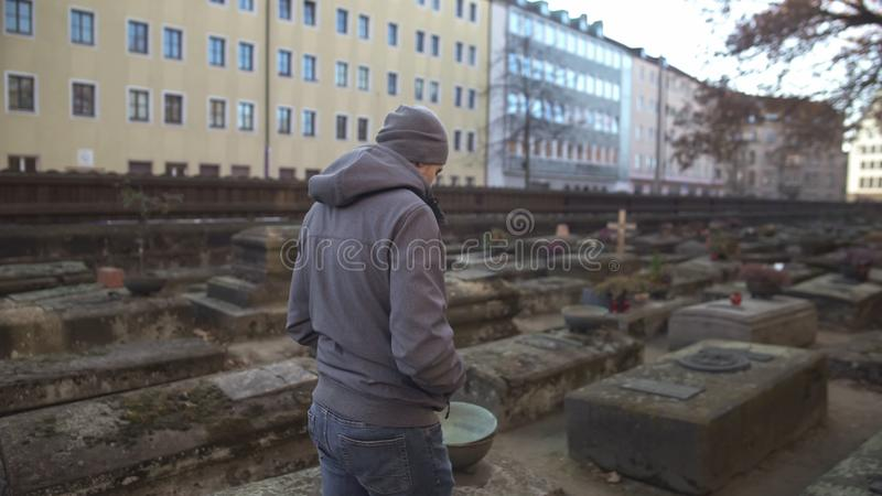 Young man walking on ancient cemetery between graves, historical place, memory royalty free stock image