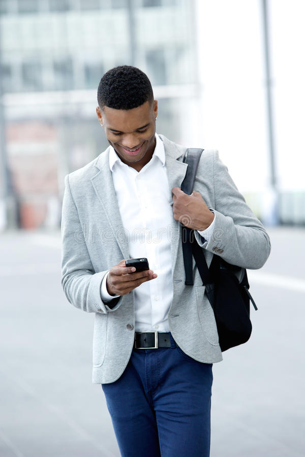 Free Young Man Walking And Looking At Mobile Phone Royalty Free Stock Images - 43803269