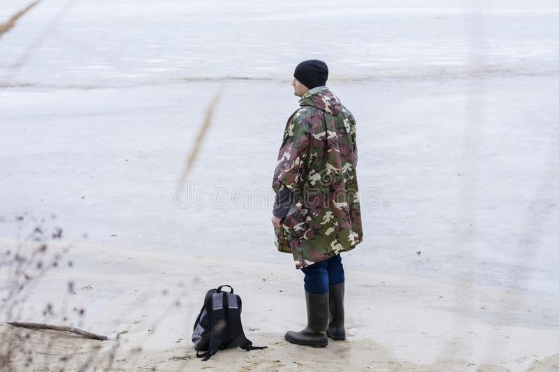 Young man walking on beach watching the frozen water in a military rain coat stock image