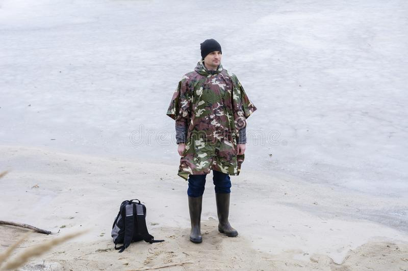 Young man walking on beach watching the frozen water in a military rain coat royalty free stock photography