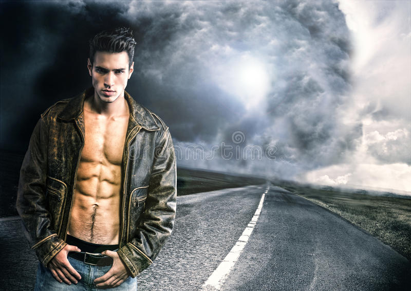 Young man walking down a road with very bad weather far away. Young man walking down a road with a storm and very bad weather far away in a distance stock photo