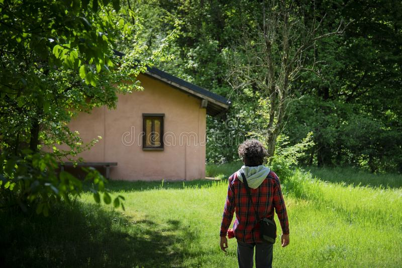 Young man walking in the green towards a pink cottage royalty free stock images