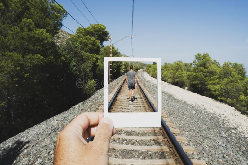 Young man walking by the railroad tracks. Closeup of a young caucasian man with a white cardboard cutout frame in his hand framing another caucasian man, seen stock photos