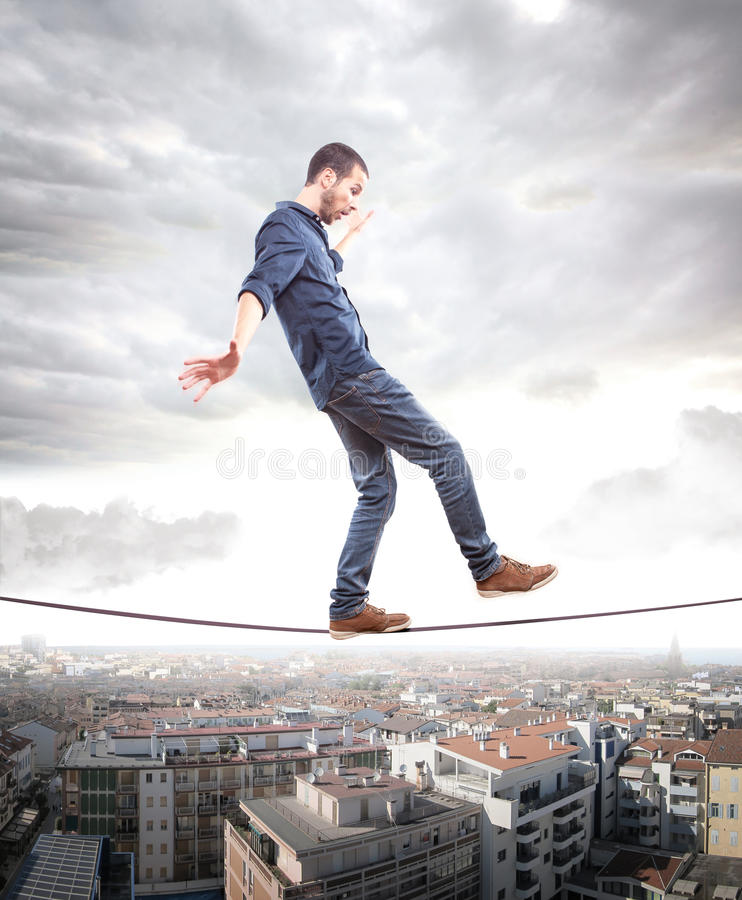 Young man walking on a rope in balance stock photography