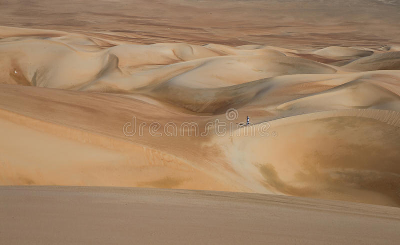 Young man walking in the sand dunes of Liwa desert royalty free stock image