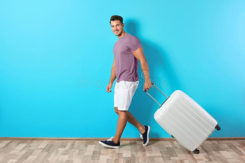 Young man walking with suitcase. On color wall background stock photo