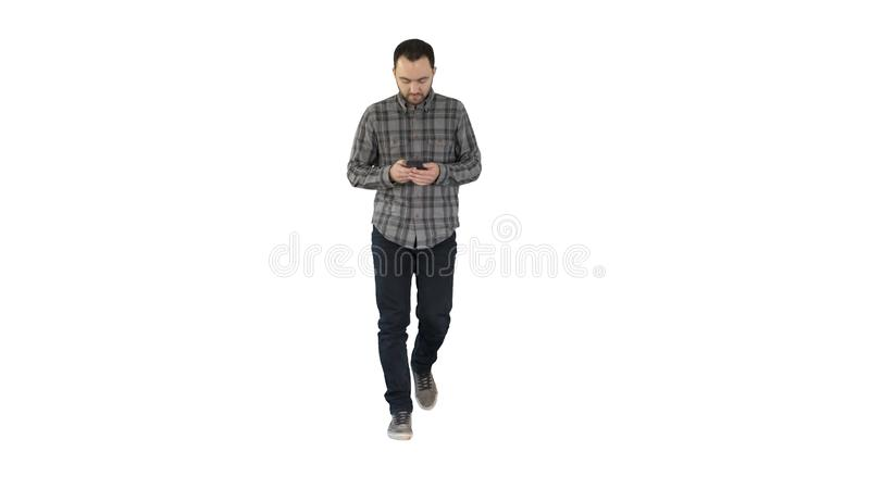 Young man walking and using a phone, messaging on white background. royalty free stock images