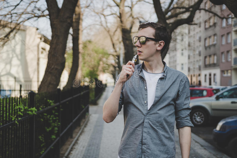 Young man walking, vaping electronic cigarette or vape. With copy space.  stock photography