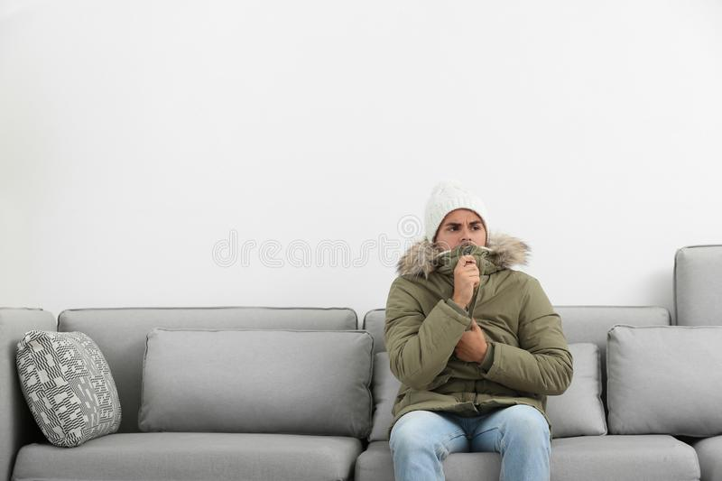 Young man in warm clothes freezing on sofa against background. Young man in warm clothes freezing on sofa against white background royalty free stock photo
