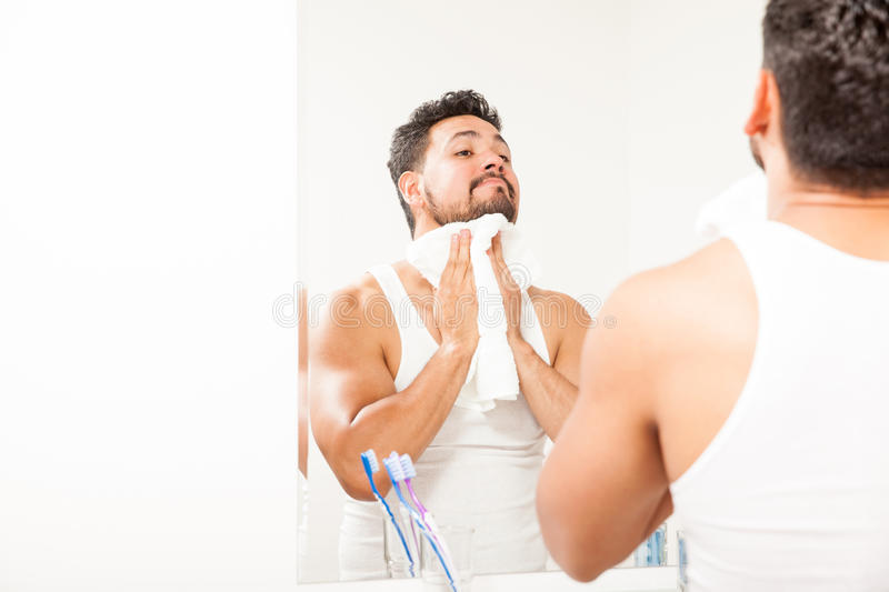 Young man washing and drying his face royalty free stock photo