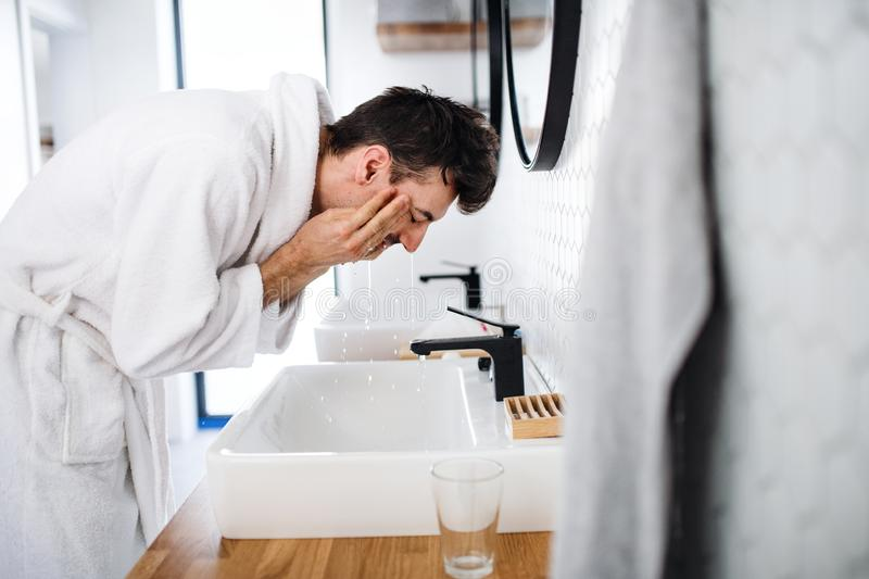 Young man washing face in the bathroom in the morning, daily routine. Young man washing face in the bathroom in the morning, a daily routine royalty free stock photo