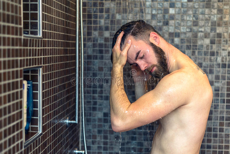 Young man washing his hair in the shower stock photos
