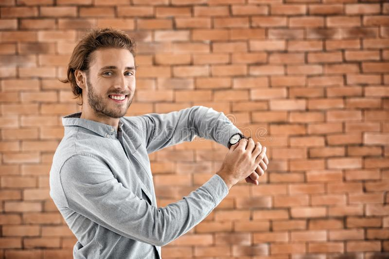 Young man with watch on brick background stock photo