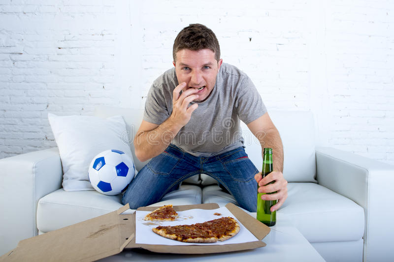Young man watching football game on television nervous and excited suffering stress biting fingernail on sofa. Couch at home with ball holding beer bottle stock images