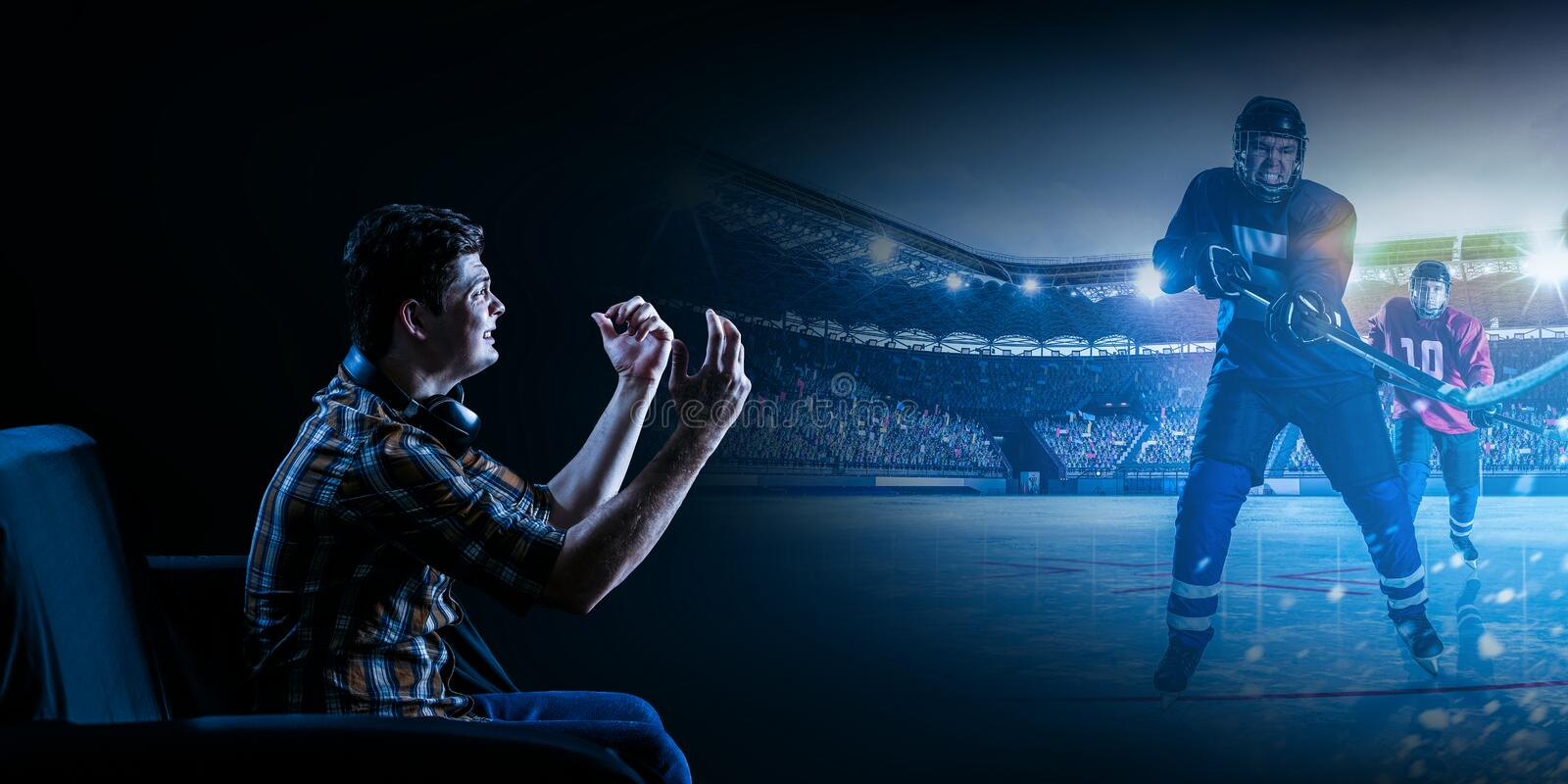 Young man watching ice hockey game on TV stock images