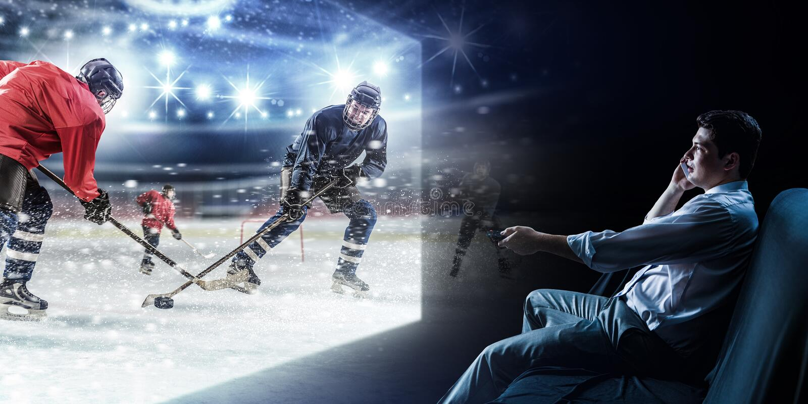 Young man watching ice hockey game on TV royalty free stock images