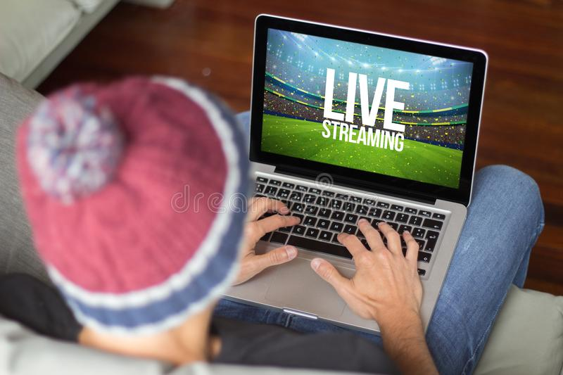 Young man on the sofa live streaming stock photo
