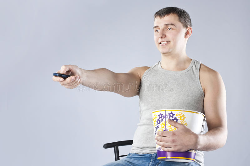 Download Young Man Watching Television With Popcorn Stock Image - Image: 26462425