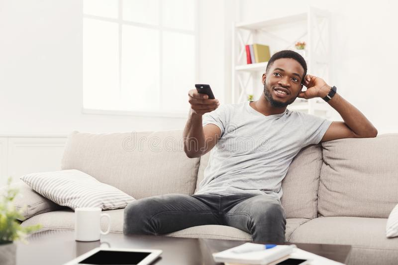 Young man watching tv using remote controller in living room. Young happy african-american man watching tv on the couch pointing with remote controller on tv-set stock images
