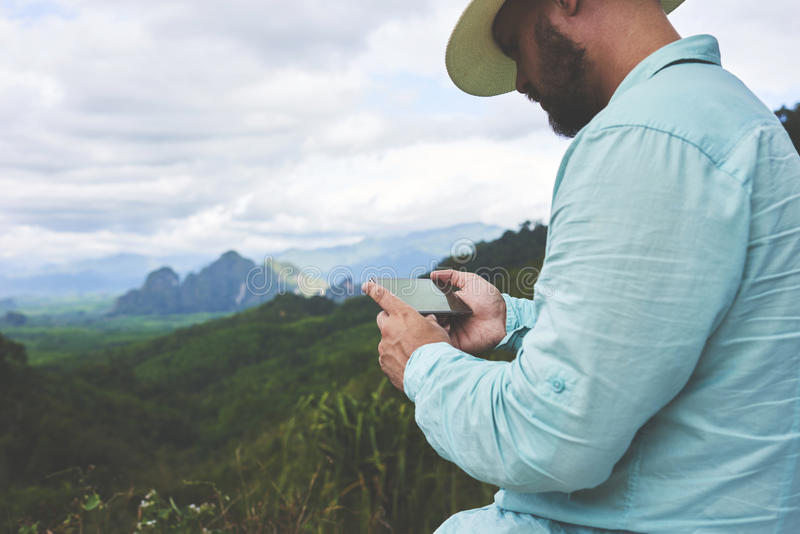 Young man is watching video which he took on cell telephone of a beautiful jungle view. Closely of a bearded hipster guy is holding smart phone with copy space stock images