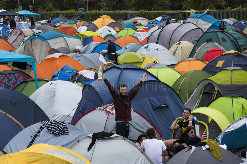 Young man waving standing in a crowdy campsite of Exit music festival. Young man saying hello after rough night in Exit campsite stock images