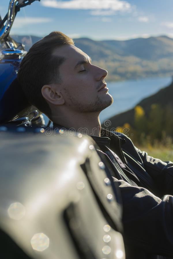 Young man wearing a black leather jacket and jeans sits outdoor royalty free stock images