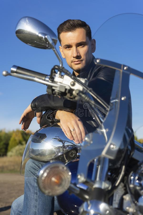 Young man wearing a black leather jacket and jeans sits outdoor stock photo