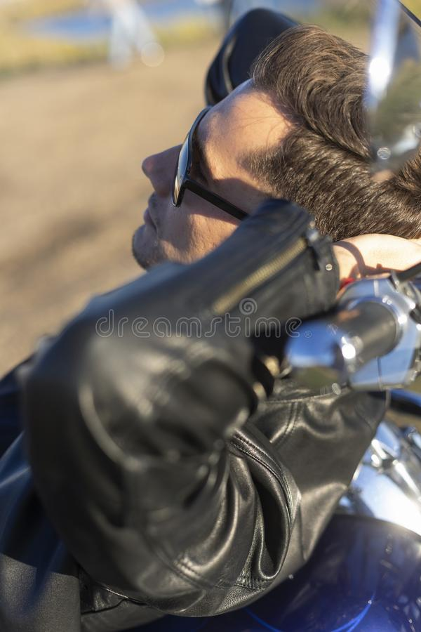 Young man wearing a black leather jacket, sunglasses and jeans l stock photography