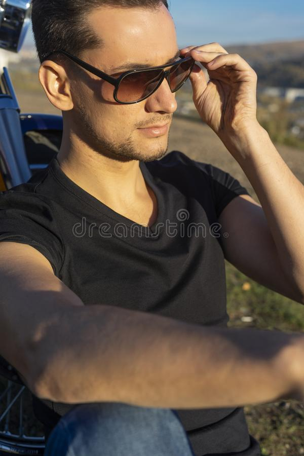 Young man wearing a black leather jacket, sunglasses and jeans s royalty free stock photo