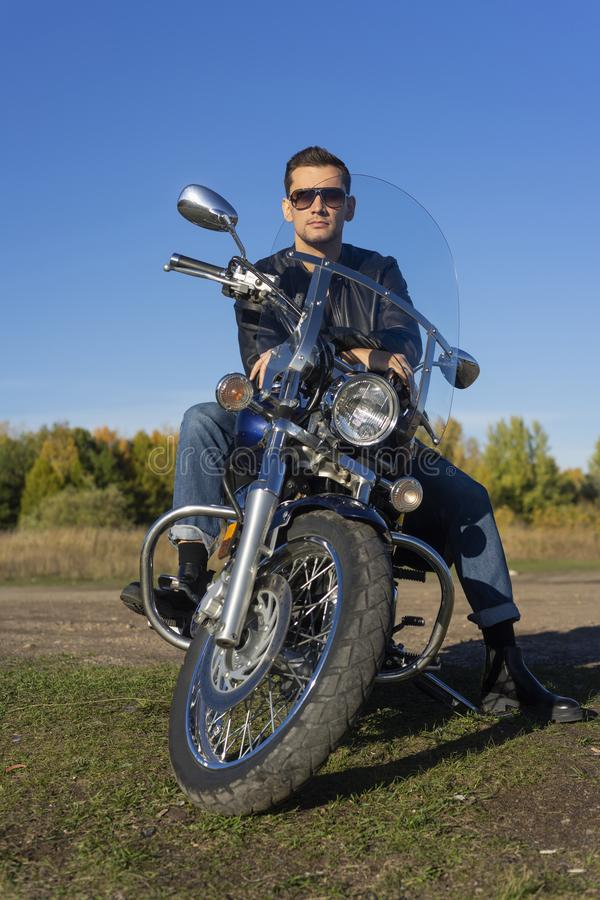 Young man wearing a black leather jacket, sunglasses and jeans s royalty free stock photography