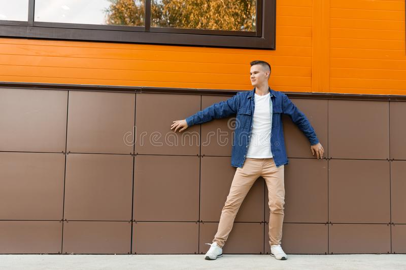 Young man wearing in a blue denim jacket and beige pants stands against the wall. Copyspace stock images