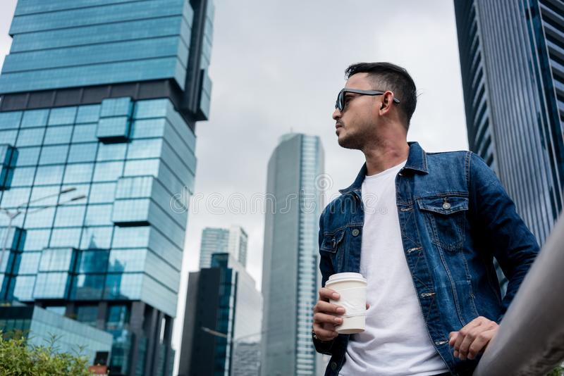 Young man wearing blue denim jacket while daydreaming outdoors i. Low angle view portrait of a young man wearing sunglasses and blue denim jacket while royalty free stock images