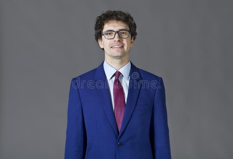Young man wearing blue suit smiling portrait royalty free stock image