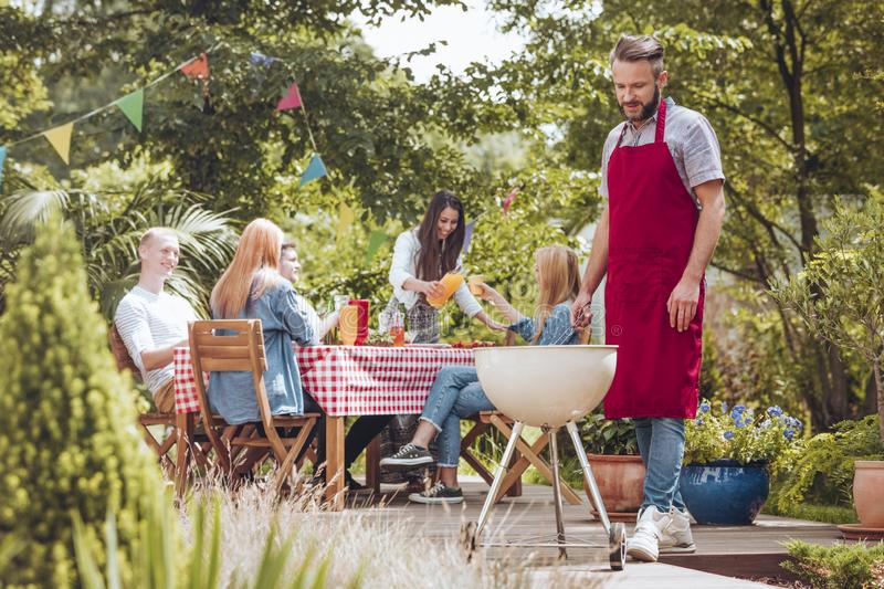 A young man wearing a burgundy apron cooking on a white grill. P. A young men wearing a burgundy apron cooking on a white grill. People sitting around a table stock photos