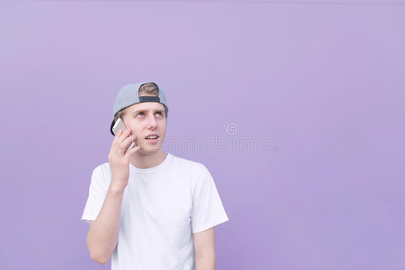 Young man wearing a cap and a white T-shirt speaks on a purple background with a marathon and looks up and down. Copyspace royalty free stock images