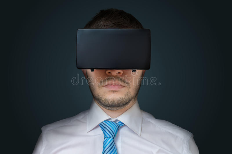 Young man is wearing 3D virtual reality glasses. Low key photo.  stock photography