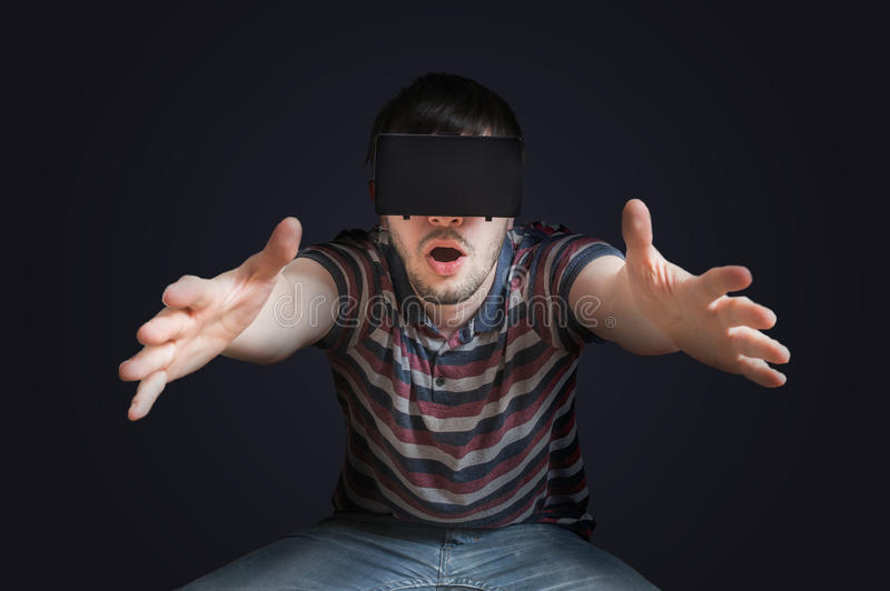 Young man is wearing 3D virtual reality glasses. Low key photo.  royalty free stock photo