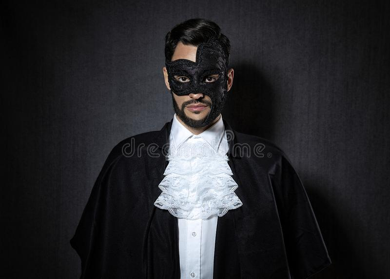 Young man wearing a dark mask, dressed in a Phantom of the Opera look royalty free stock photos