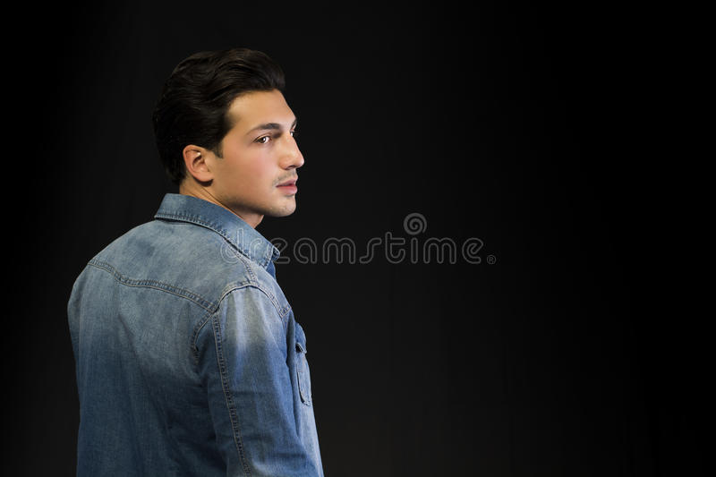 Young man wearing denim shirt seen from the back, looking to a side stock photo