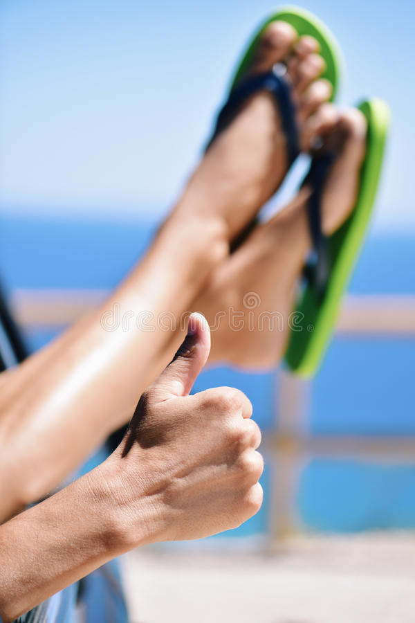 Young man wearing flip-flops relaxing in a car near the ocean. Closeup of of a young caucasian man wearing flip-flops relaxing in a car near the ocean, giving a royalty free stock images