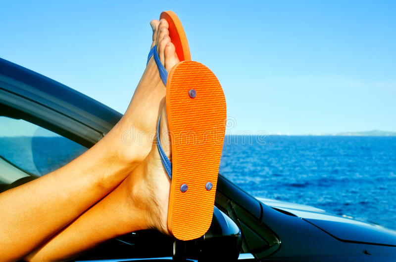 Young man wearing flip-flops relaxing in a car near the ocean. Detail of the feet of a young man wearing flip-flops who is relaxing in a car near the ocean stock photography
