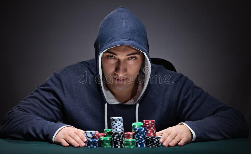 Young man wearing a hoodie with cards and chips gambling. The young man wearing a hoodie with cards and chips gambling stock images