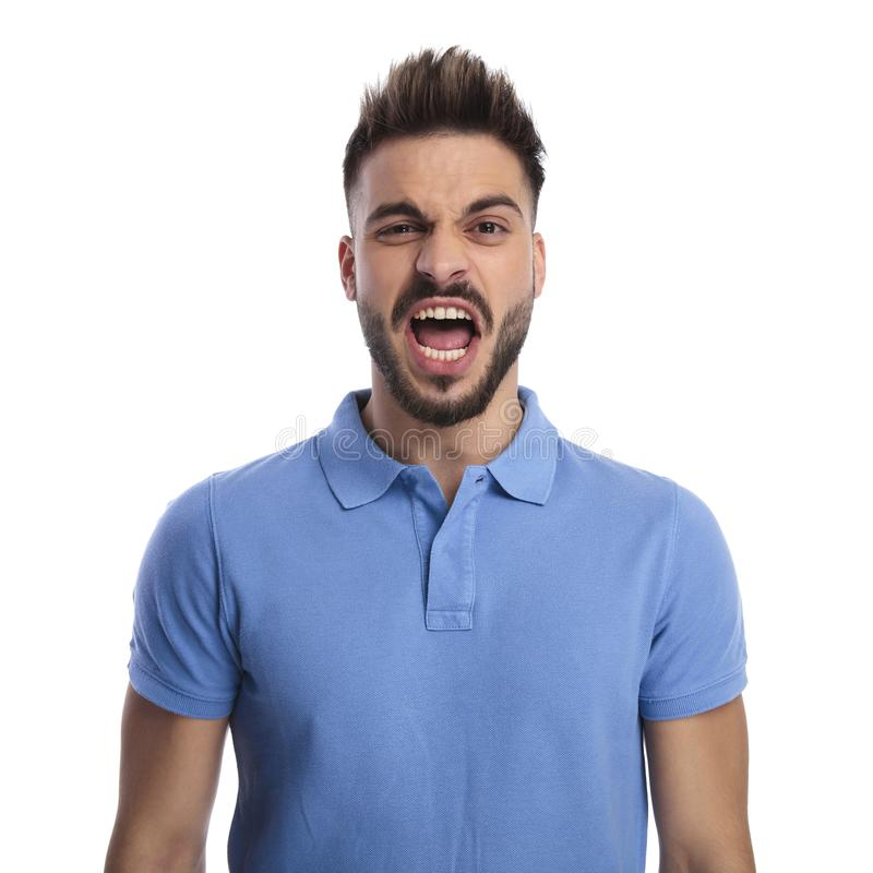 Young man wearing a light blue polo shouting out loud. While looking at the camera on a light background royalty free stock photo