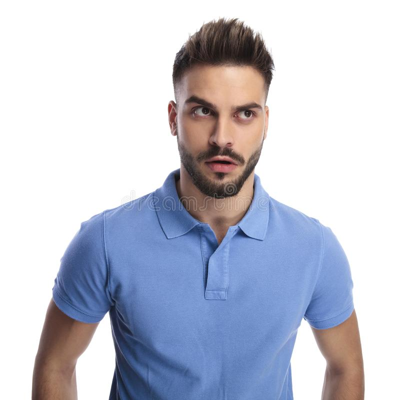 Young man wearing a light blue polo trying to remember something. While looking upwards and to a side on a light background royalty free stock image