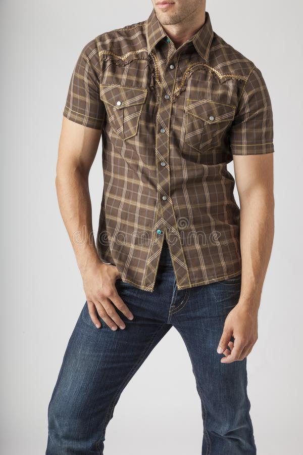 Young man wearing plaid western wear shirt and denim jeans. Men`s trendy casual clothing fashions styles. Young man wearing plaid western wear shirt and denim royalty free stock photo
