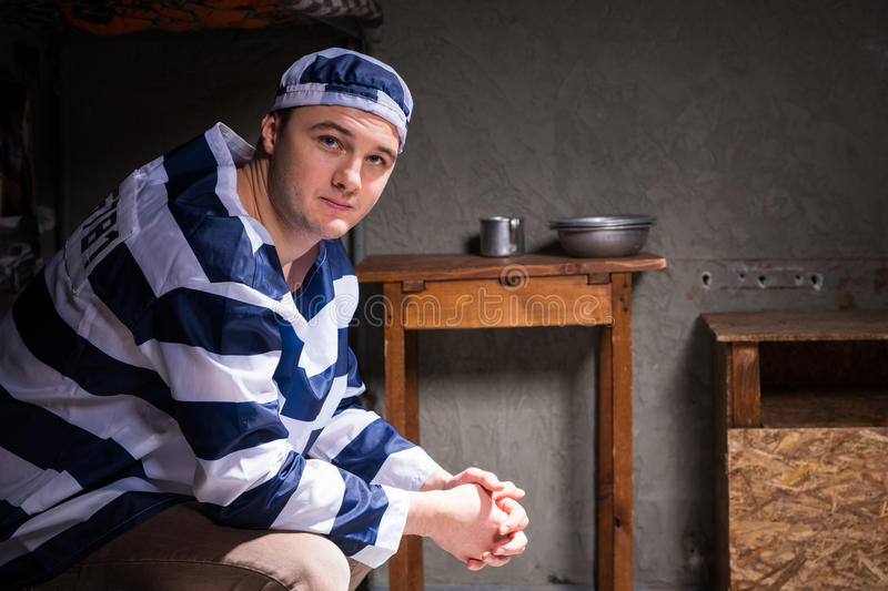 Young man wearing prison uniform sitting on a bed in a small prison cell stock images