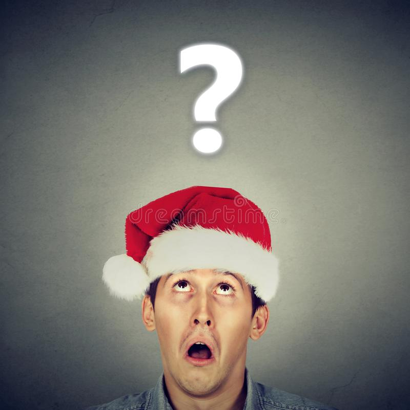 Man in Santa hat questioning about gifts royalty free stock image